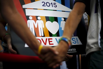 A couple hold hands at a celebration rally in West Hollywood
