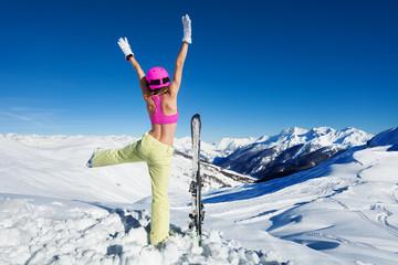 Strong female skier having fun on mountain peak