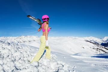 Cool female skier looking at snowy peaks