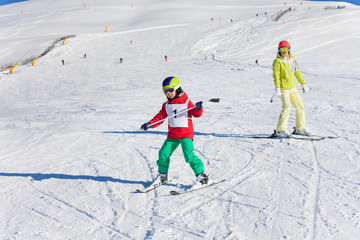 Boy learning downhill skiing with instructor