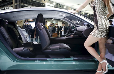 Visitors takes photographs of a Kia Motor's concept car Novo as a model poses at the Seoul Motor Show 2015 in Goyang