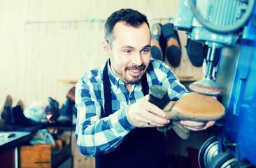 Man worker restore footwear in repair workplace