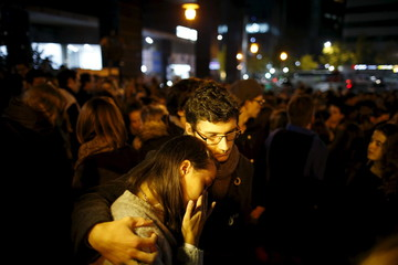 French couple react as they pay tribute to the victims of Paris attacks in front of the French embassy in Seoul
