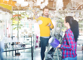 Man and girl choosing modern chandelier