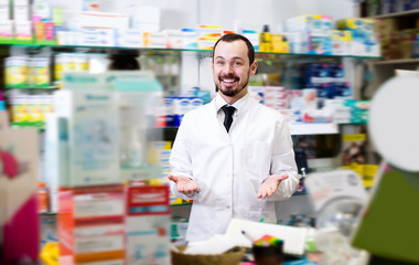 Handsome man pharmacist showing assortment