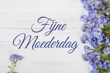 Mother's day card with Dutch words: Happy Mother's day. Blue flowers frame on white wooden background