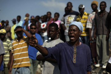 An earthquake survivor yells slogans against riot policemen as they block the main road to the airport during a rally in Port-au-Prince