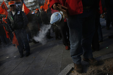 Beekeper blows smoke during protest by farmers and stockbreeders against cuts in their sectors, in Madrid