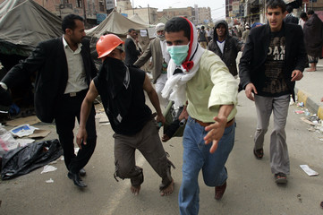 People carry an injured protester to a makeshift clinic after clashes with police in Sanaa