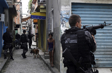 A girl looks on as policemen take positions during an operation in the Mare slums complex in Rio de Janeiro
