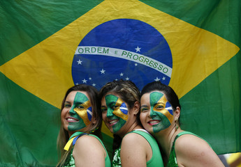 Fans of Brazil pose for pictures as they wait for the start of their 2014 World Cup semi-finals against Germany at the Mineirao stadium in Belo Horizonte