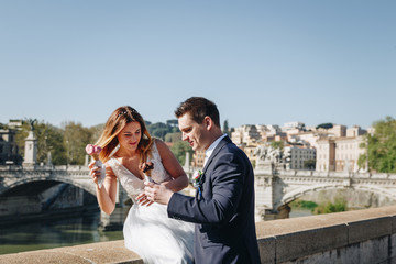 Bride and groom wedding poses with ice-cream in Vatican on the bank of the river Tiber, Rome, Italy