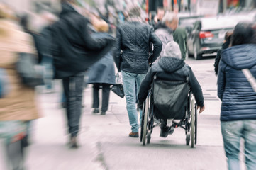 Disabled man sitting in a wheelchair on a busy street