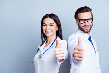 Two successful doctors in uniform together showing thumbs-up on gray background