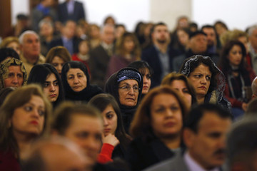 Iraqi Christians, who fled with their families from violence in their country, pray during a mass on Christmas Eve at Saint George Victorious Cathedral in Amman