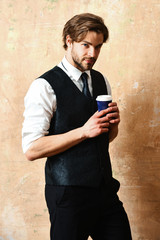 morning coffee, young serious business man holding paper cup