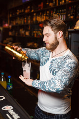 Bearded barman prepares a cocktail seriously