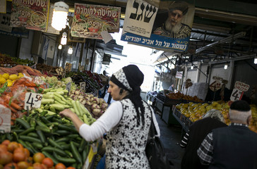 A woman shops for vegetables under a campaign banner depicting Rabbi Ovadia Yosef in Tel Aviv