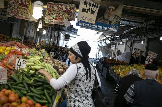 A woman shops for vegetables under a campaign banner depicting Rabbi Ovadia Yosef in Tel Aviv
