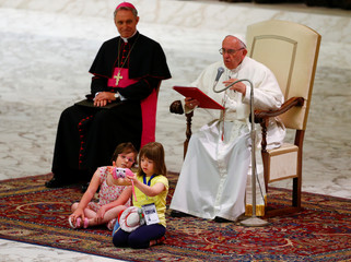 A child takes pictures as she sits in front of Pope Francis during a special audience during a Jubilee for the sick and disabled in Paul VI hall at the Vatican