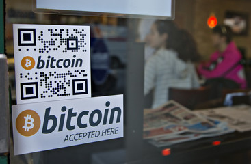 Signs on window advertise bitcoin ATM machine that has been installed in a Waves Coffee House in Vancouver