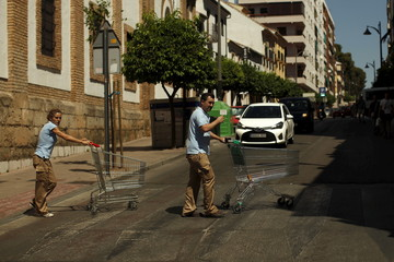 Workers of a supermarket push shopping carts in downtown Ronda