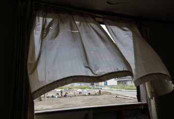 Volunteers clearing a site devastated by March 11's earthquake and tsunami are seen through a window at a damaged house in Sendai