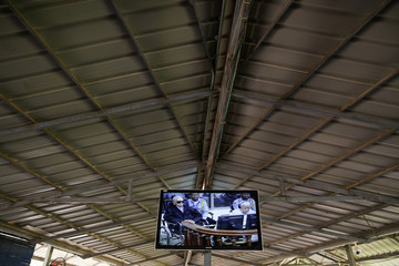 Former Khmer Rouge head of state Samphan and former Khmer Rouge leader Chea appear on the screen as people watch the delivery of the verdict in their trial on the outskirts of Phnom Penh