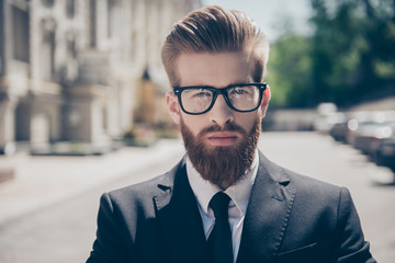Close up portrait of a successful young red bearded guy in suit and glasses. So stylish and nerdy. Outdoors on a sunny street