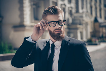 Nerdy hot bearded guy in a formal wear and glasses outside. He is so harsh and mature, stylish and fashionable