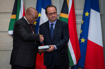 French President Francois Hollande gives an audio recording of Nelson Mandela to South Africa's President Jacob Zuma before a joint press conference at the Elysee Palace in Paris