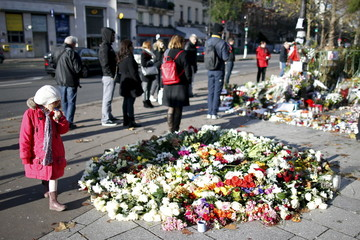 A girl looks at flowers, candles and messages left in memory of victims near the Bataclan concert hall, one of the sites of last Friday's deadly attacks, in Paris, France
