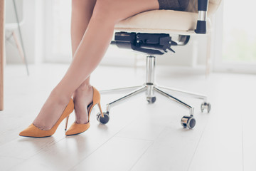 Close up cropped photo of beautiful legs of the business lady in high hills shoes. she is sitting in the office