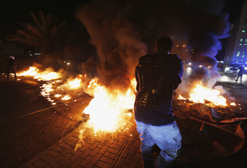 A riot police officer removes burning tyres from highway set up by anti-government protesters in Diraz