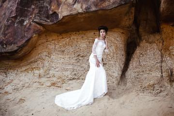 bride in wedding dress  in desert with rocks and stones