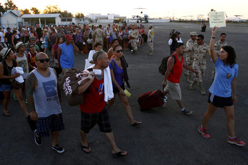 Stranded tourists follow a U.S. Consulate employee after being airlifted by the Mexican Army from Los Cabos, at the international airport of Tijuana