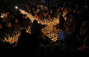 Worshippers gather around candles during a mass in Blagoevgrad