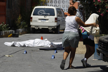 Woman covers her daughter with a towel as they walk past a crime scene in the municipality of San Nicolas de los Garza