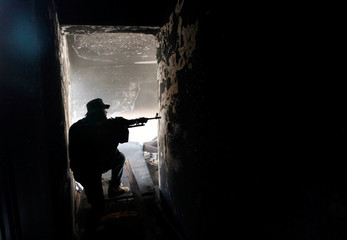 Fighter of Libyan forces allied with the U.N.-backed government aims his weapon as he takes up position inside a ruined house at the front line of fighting with Islamic State militants in Ghiza Bahriya district in Sirte