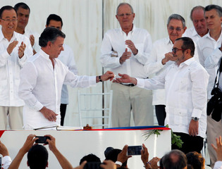 Colombian President Santos hands a lapel pin in shape of a dove to Marxist rebel leader Londono, better known by the nom de guerre Timochenko, after signing an accord ending a half-century war that killed a quarter of a million people in Cartagena