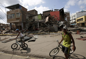 Residents hold their bicycles as damaged and collapsed buildings are seen in the background after an earthquake struck off the Pacific coast, in Portoviejo