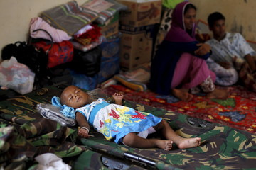 A Rohingya child, who recently arrived in Indonesia by boat, sleeps inside a shelter in Kuala Langsa