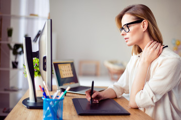 Concentrated young woman in glasses retouching photo for a long time and having  pain in her neck