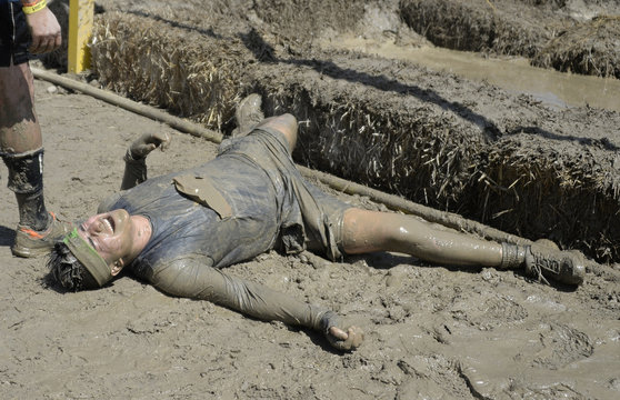 """A man reacts as he crosses the finish line during the """"Tough Mudder"""" obstacle course event in San Bernardino, California"""