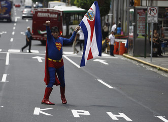 A demonstrator holds up a Costa Rican national flag during a march with public workers against the corruption in San Jose