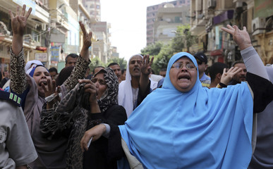 Relatives and families of supporters of ousted President Mursi do the Rabaa sign near security forces in Minya