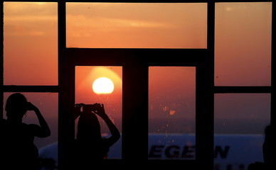 Tourist photograph the sunrise at the airport terminal on the Greek island of Santorini