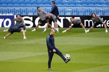 Barcelona's coach Pep Guardiola controls a ball during a training session at Real Madrid's Santiago Bernabeu stadium in Madrid
