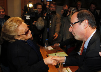 Francois Hollande, President of the General Council of Correze and Socialist party member, shakes hands with Bernadette Chirac before his reelection at the General Council of Correze in Tulle