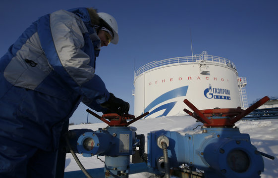 A worker checks a valve at the Gazpromneft company owned Yuzhno-Priobsky gas processing plant, with an oil tank seen on the background